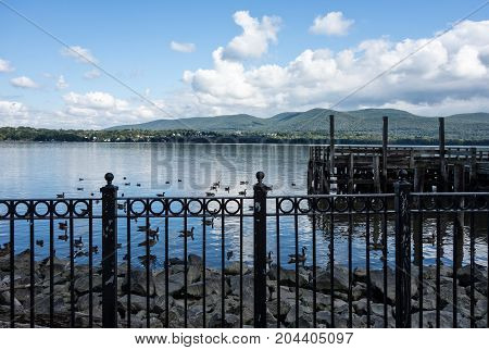 A scenic view of the Hudson River seen from the Newburgh waterfront. A black iron fence ducks and wooden dock are seen under a blue sky with white clouds and the Mt. Beacon mountain in the background.