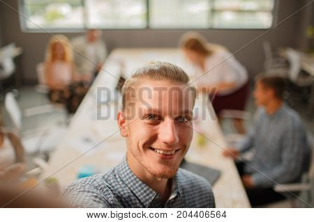 Smiling and beautiful man on his work with colleagues.