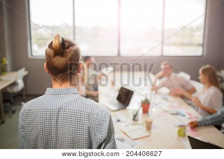 Back of handsome young and stylish businessman in office.