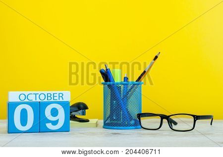 October 9th. Day 9 of month, wooden color calendar on teacher or student table, yellow background . Autumn time. Empty space for text.