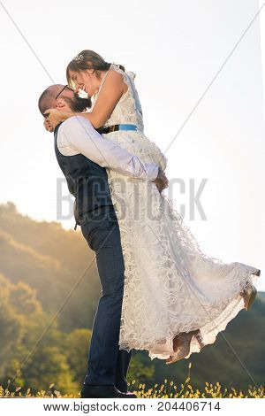 Groom Holding Bride In His Arms