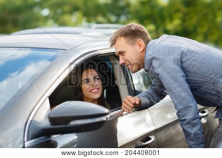 Buying used car. Car Dealer Inventory. Used cars store. Male wants to buy the car for his young wife. Happy life. Blur background.