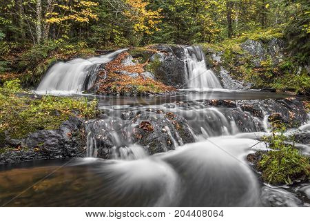 Lower Duppy Falls flows over leaf-covered volcanic rocks in a beautiful remote autumn wood of Michigan's western Upper Peninsula.