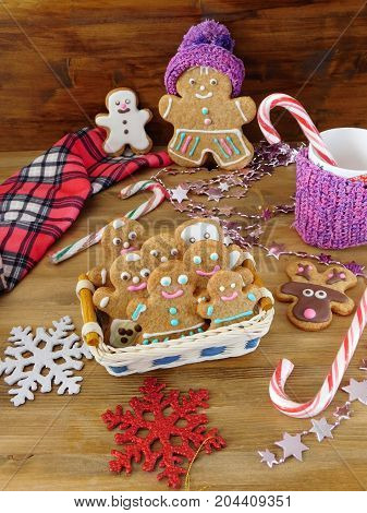 Gingerbread men cookies in a wicker basket surrounded by Christmas decorations