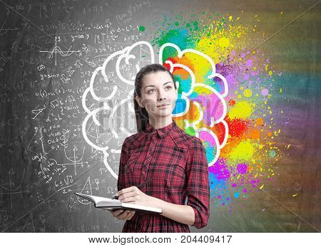 Portrait of a young woman with long dark hair wearing a red dress and holding a planner and a pen. Blackboard background with a colorful brain sketch and formulas