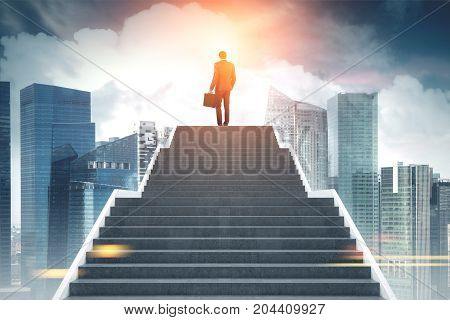 Rear view of a young businessman with a suitcase on the top of stairs. A magnificent modern city background. Concept of a road to success. Toned image