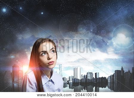 Portrait of a dreamy young woman with full lips and long fair hair. She is looking upwards and thinking against a night cityscape background. Mock up