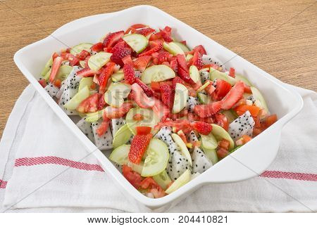 White Porcelain Tray of Fruits Salad Strawberries and Dragon Fruit with Cucumbers and Tomatoes.