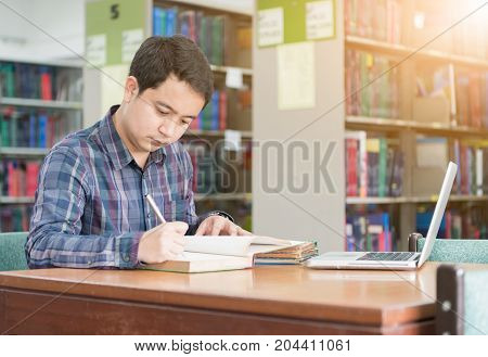 Young Student Taking Notes From A Book At Library