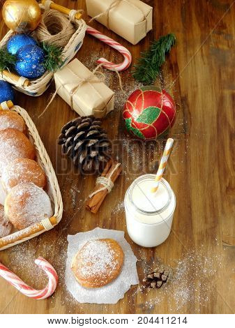 Milk in a glass jar with a straw surrounded by Christmas attributes and doughnuts. View from above