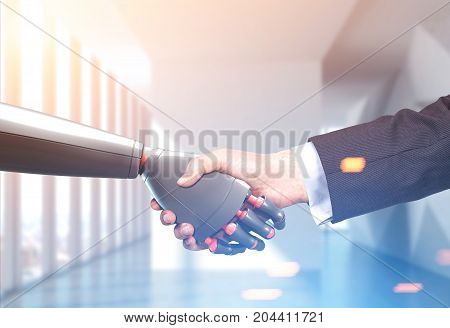 Close up of a businessman in a suit and a robot shaking hands. Office background. Concept of innovation in business. Toned image