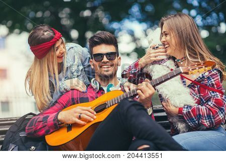 Friends in the park having fun playing guitar