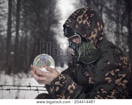 Army soldier in camouflage uniform and a gas mask. A military man looks at a transparent ball with a Christmas landscape - snow house winter