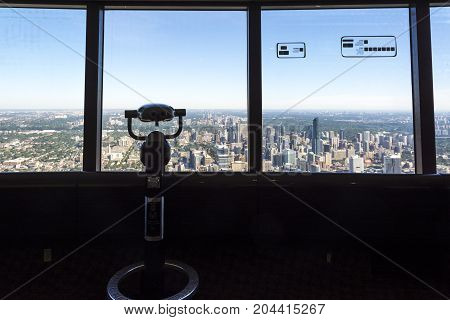 TORONTO,CANADA-AUGUST 2,2015:binoculars and view of Toronto city skyline from the top of the Cn tower during a sunny day.