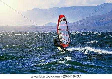 Sportman windsurfer on the lake surface at sunset time. Nahuel Huapi lake by San Carlos de Bariloche at windy day time. North Patagonia. Argentina.
