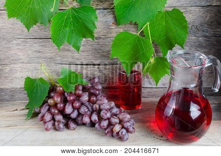 Vine decanter and a glass of grape juice on a background of green leaves and old boards