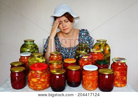 Sad woman with headache sits with a homemade preserves