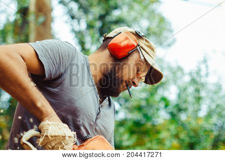 industry building technology and people concept - male builder in hardhat with walkie talkie or radio outdoors
