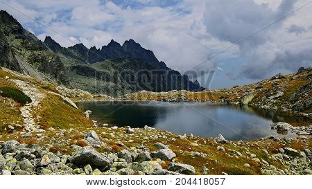 High Tatras in Slovakia. Monumental peaks. Summer scenic landscape mountain view. Alpine trail. Prostredny hrot and Starolesnianske tarn in Big cold valley.