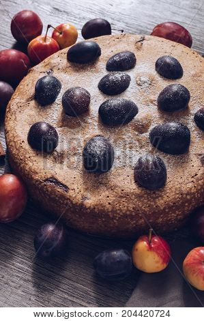 Fruit pie with plums and apples on a wooden table
