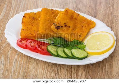 Fish In Breadcrumbs, Lemon, Cucumbers, Tomatoes, Parsley On Dish
