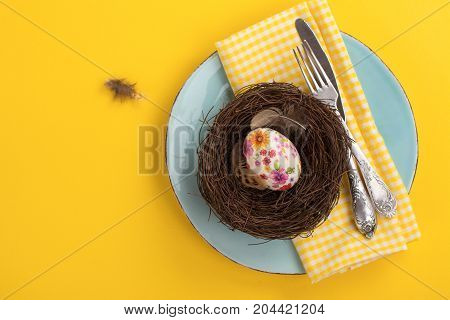 Spring Easter table setting with plate, decorative nest, egg, silverware and napkin. Space for text