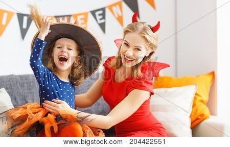 family mother and child girl daughter getting ready for halloween putting on costumes