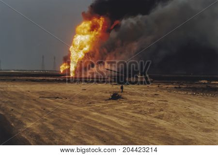 Oil Well Burning In Field With Remains Of Burned Tank