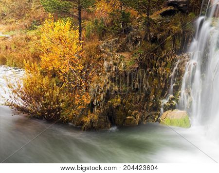 Small waterfall in the mountains. Autumn nature