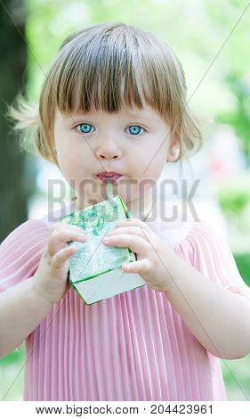 beautiful blue-eyed girl drinks juice from a straw on a nature background
