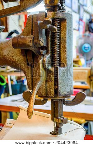 Fragment of the old heavy sewing machine. Clothing industry. Sewing workshop.
