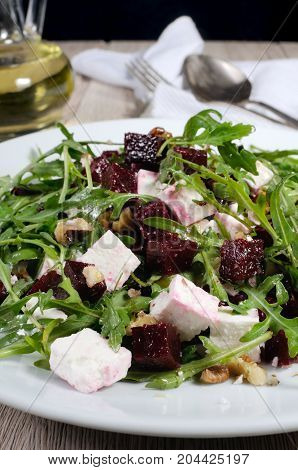 Salad from roasted beets arugula cheese feta and walnuts. Vertical shot. Foreground