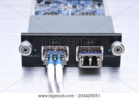 Gigabit interface converter with optical network cables on metal grey background