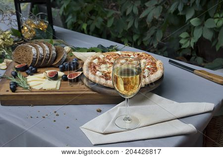 Pizza on board, cheese, bread and glass of wine on the table