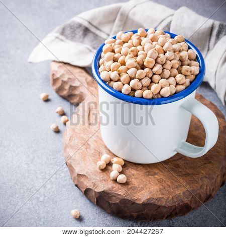 Raw uncooked organic chickpeas in white enamel mug on rustic wooden board on light gray stone background. Healthy vegan vegetarian food concept with copy space.
