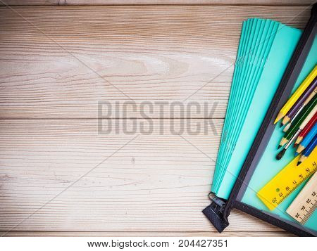 Pile of notebooks and school supplies on the wooden background. School concept