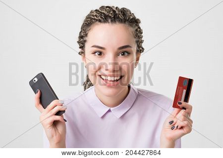 Happy caucasian european young woman holding phone and card making order online. Internet bank and online shopping technology concept