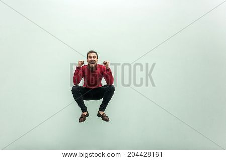 Like A Frog. Jumping Higher. Bearded Man In Red Shirt Celebrating Hes Victory, Looking At Camera And