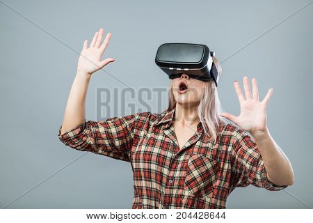 Young cheerful woman with virtual reality headset