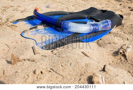 swimming snorkel and fins lying on the sand