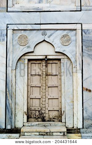 Old mughal architecture wooden door set in a beautiful archway in a marble wall