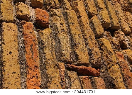 Close-up of an old stone wall with fragments of brick. With selective fokus