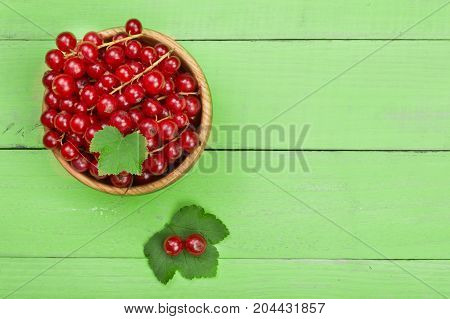 Red currant berries in a wooden bowl with leaf on the green wooden background with copy space for your text. Top view.