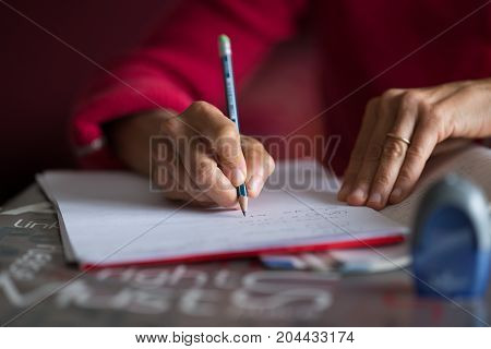 Hand writing on paper with pencil on desk. Selective focus on pencil home interior very shallow depth of field.