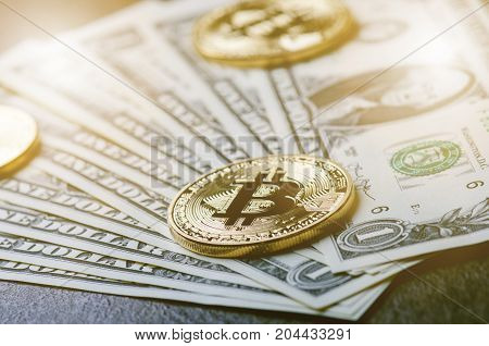 Golden bitcoin coins on a paper dollars money and dark background with sun. Virtual currency. Crypto currency. New virtual money Dollars money. Lens flare