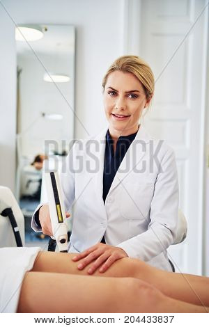 Smiling Clinic Technician Performing Electrolysis On A Client's Leg