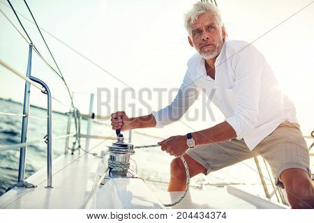 Mature Man Using A Winch While Sailing On The Ocean