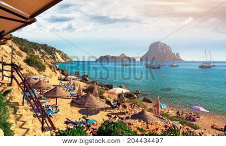 Small Cala d'Hort beach with a fantastic view of the mysterious island of Es Vedra. Ibiza Island Balearic Islands. Spain