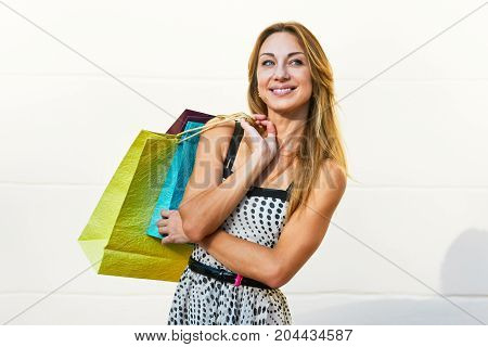Portrait of smiling glad woman holding paperbags after shopping