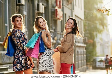 Three happy smiling girlfriends holding colorful shopping bags